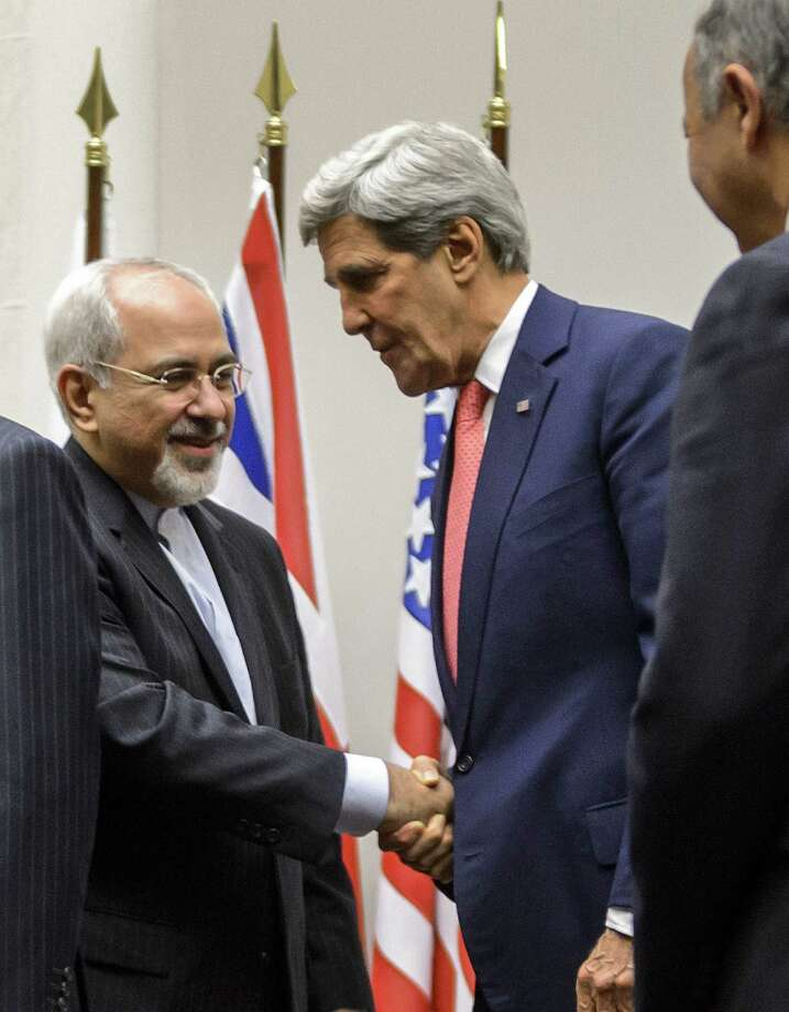 Iranian Foreign Minister Mohammad Javad Zarif (left) shakes hands with Secretary of State John Kerry after world powers on Nov. 24 agreed to a landmark deal with Iran halting parts of its nuclear program. Photo: Fabrice Coffrini / AFP / Getty Images