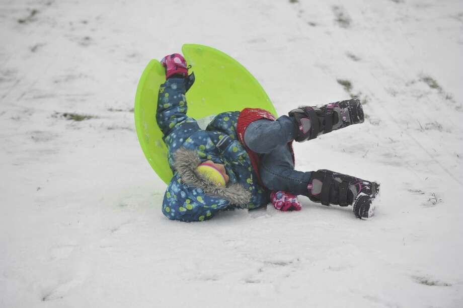 Amanda Diaz does a slow-motion wipe-out while sledding down a hill at E. Gaynor Brennan Municipal Golf Course after the first snow accumulation in Stamford, Conn., on Tuesday, Dec. 10, 2013. According to the National Weather Service at 11 a.m. the snow total for Stamford reached 1.5 inches. Photo: Jason Rearick / Stamford Advocate