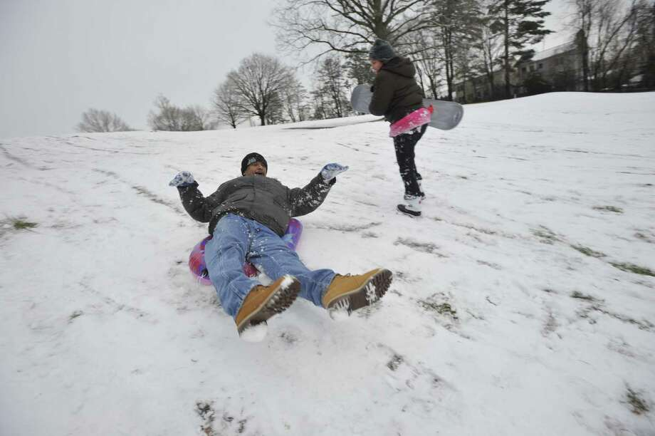 Edwin Diaz sleds down a hill as his daughter, Krystal, walks back up at E. Gaynor Brennan Municipal Golf Course after the first snow accumulation in Stamford, Conn., on Tuesday, Dec. 10, 2013. According to the National Weather Service at 11 a.m. the snow total for Stamford reached 1.5 inches. Photo: Jason Rearick / Stamford Advocate