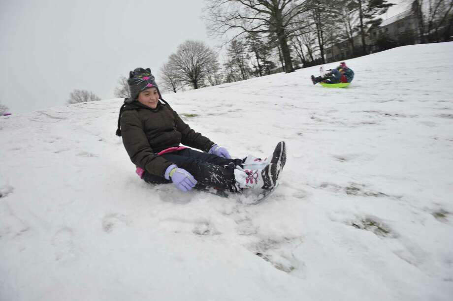 Krystal Diaz, left, and her sister, Amanda, sled down a hill at E. Gaynor Brennan Municipal Golf Course after the first snow accumulation in Stamford, Conn., on Tuesday, Dec. 10, 2013. According to the National Weather Service at 11 a.m. the snow total for Stamford reached 1.5 inches. Photo: Jason Rearick / Stamford Advocate