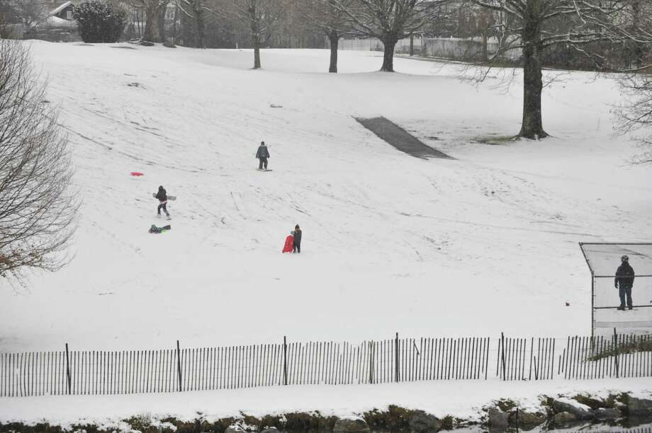 Children and parents sled down a hill at E. Gaynor Brennan Municipal Golf Course after the first snow accumulation in Stamford, Conn., on Tuesday, Dec. 10, 2013. According to the National Weather Service at 11 a.m. the snow total for Stamford reached 1.5 inches. Photo: Jason Rearick / Stamford Advocate