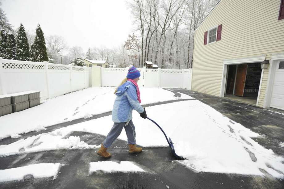 Cira Mancuso shovels her family's driveway after the first snow accumulation in Stamford, Conn., on Tuesday, Dec. 10, 2013. According to the National Weather Service at 11 a.m. the snow total for Stamford reached 1.5 inches. Photo: Jason Rearick / Stamford Advocate
