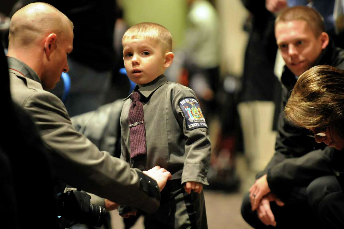 Reese Mayhew, 3, of Horseheads, N.Y., center, gets fixed up from his father, Brian Mayhew, left, during the New York State Police Academy graduation on Tuesday, Dec. 10, 2013, at the Empire State Plaza Convention Center in Albany, N.Y. Reese's mother, Tabitha Mayhew was among the graduating state troopers. (Cindy Schultz / Times Union)