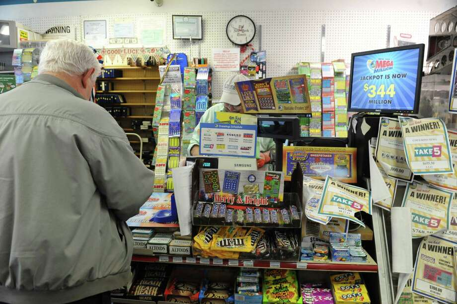 Richard Kent of Latham buys his lottery tickets from Fershid Hushmendy  owner of Coulson's news center on Tuesday, Dec. 10, 2013 in Latham, N.Y. The Mega Millions jackpot is $344 million. (Lori Van Buren / Times Union) Photo: Lori Van Buren / 00024981A