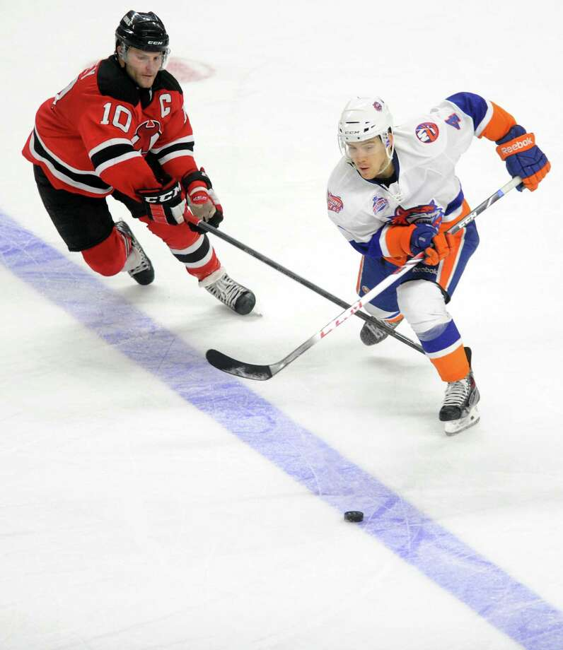 Bridgeport's Mike Cornell passes the puck as Albany's Rod Pelley defends during the Sound Tigers game Tuesday, Dec. 10. 2013 at the Webster Bank Arena in Bridgeport, Conn. Photo: Autumn Driscoll / Connecticut Post