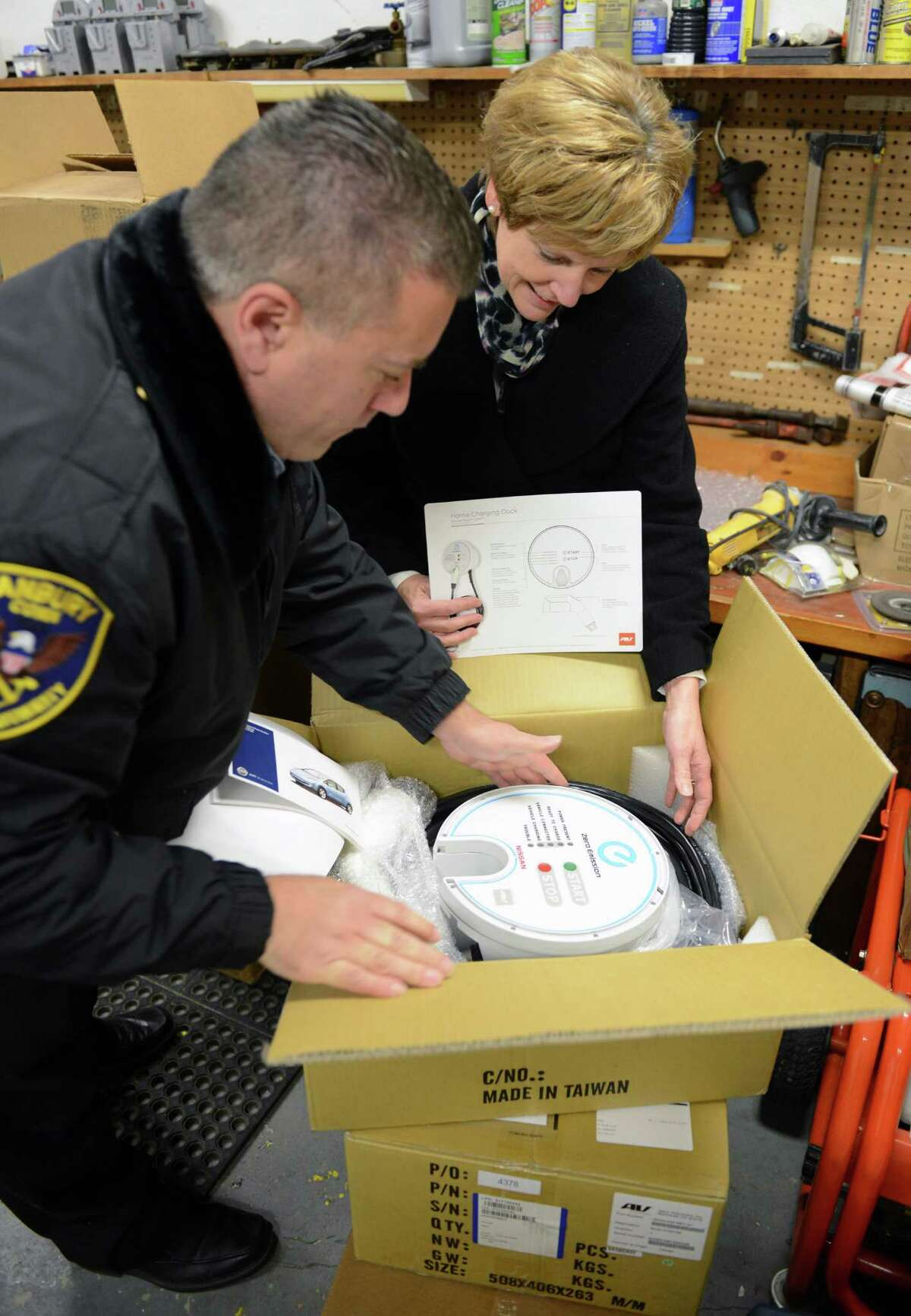 Danbury Parking Authority Enforcement Office George Marasco and Danbury Parking Authority Director Debbie Pacific open up a package containing a new donated electric car charging station that will eventually be installed in the Patriot Garage in Danbury, Conn. on Tuesday, Dec. 10, 2013.