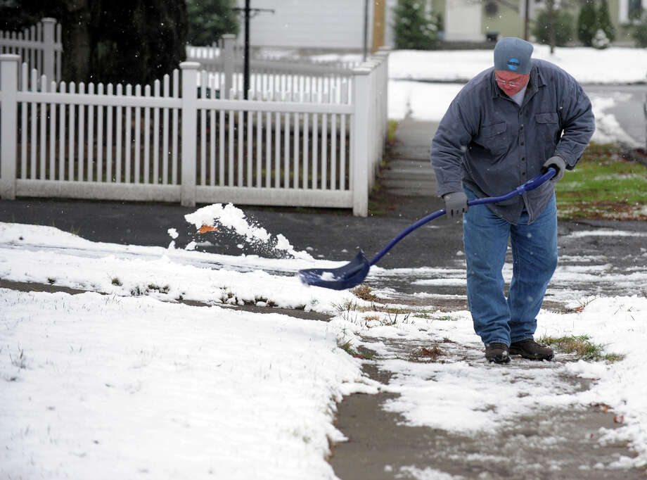 Michael McFadden shovels the little bit of snow that fell in front of his house on Elton Street in Milford, Conn. on Tuesday December 10, 2013. Photo: Christian Abraham / Connecticut Post