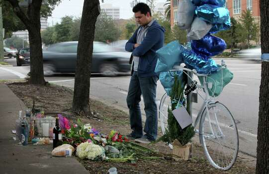 Fernando Marron leaves flowers, bread and wine at the memorial for friend Chelsea Norman, 24, the cyclist who was hit by a motorist Dec. 1st near the corner of Waugh and West Gray on Monday, Dec. 9, 2013, in Houston. Photo: Mayra Beltran, Houston Chronicle / © 2013 Houston Chronicle