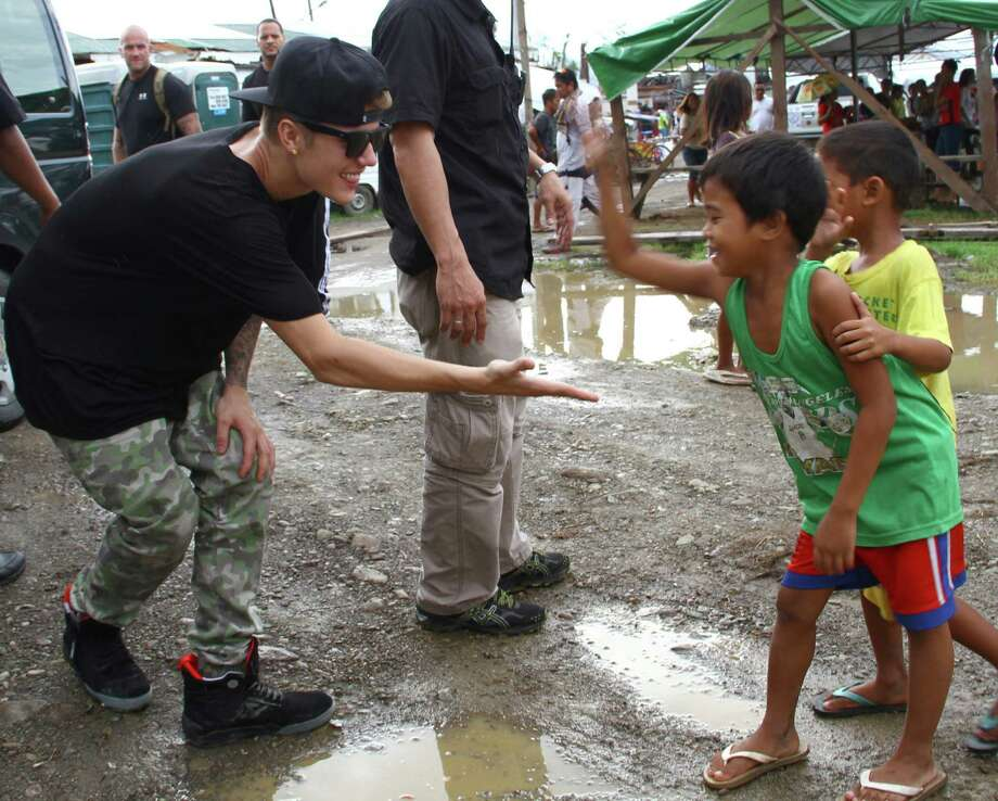 Justin Bieber, left, exchanges high-fives with children survivors of typhoon Haiyan during his visit Tuesday, Dec. 10, 2013 to Tacloban city, Leyte province in central Philippines. The teen heartthrob Bieber arrived Tuesday in the Philippines, where he has launched a campaign to help victims of last month's killer typhoon. (AP Photo) ORG XMIT: XBM114 / AP