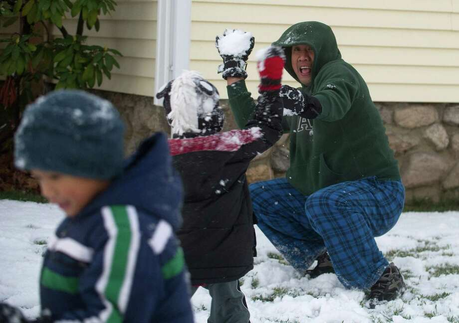 Chris Antipuesto throws snowballs with his sons, Ancel, 5, and Alec, 6, at their Hope Street home on Tuesday, December 10, 2013. Photo: Lindsay Perry / Stamford Advocate