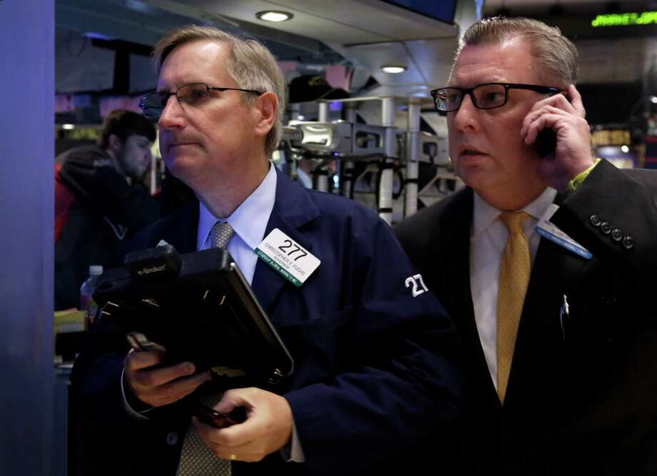 In this Tuesday, Dec. 3, 2013, photo, traders Christopher Fuchs, left, and Matthias Roberts work on the floor of the New York Stock Exchange. World stock markets were muted Tuesday, Dec. 10, 2013 as profit taking offset mildly positive economic indicators from China. (AP Photo/Richard Drew) ORG XMIT: NYBZ117 Photo: Richard Drew / AP