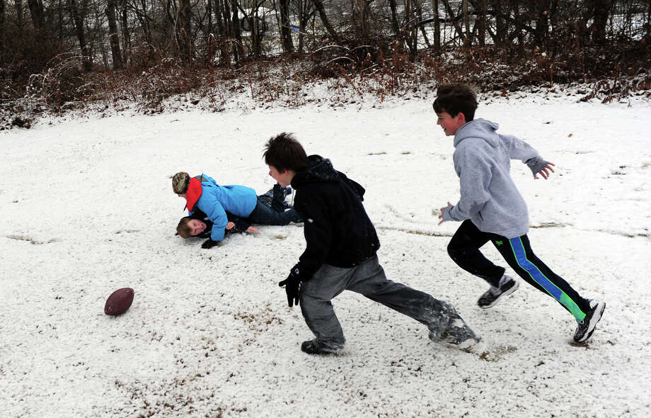 Neighborhood boys play football in the snow at Wilcox Park in Milford, Conn. on Tuesday December 10, 2013. Photo: Christian Abraham / Connecticut Post
