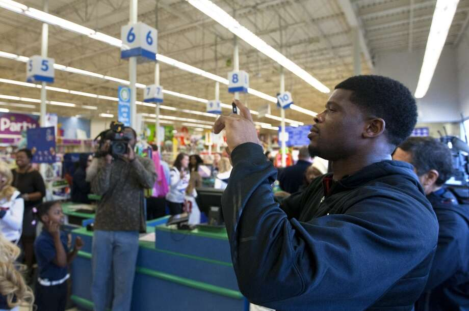Texans wide receiver Andre Johnson takes a photo as his annual shopping spree on Tuesday. Kids, ages 8 to16 from Child Protective Services were given 80 seconds to run through the store and fill their carts with as much as they could. Johnson spent $17,300.52 for the kids. Photo: Cody Duty , Houston Chronicle
