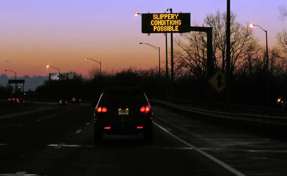 A highway sign warns drivers of slippery conditions along I95 southbound in Stratford, Conn. on Tuesday December 10, 2013. Photo: Christian Abraham / Connecticut Post