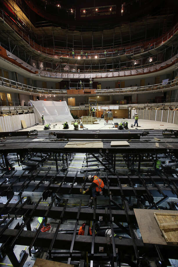 Workers install the flooring system during early construction on the Tobin Center on November 26, 2013. The photograph shows the view from the stage. Photo: TOM REEL