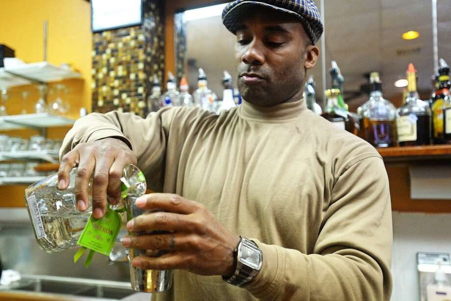 Former Atlanta Falcons wide receiver Floyd Dixon Jr. prepares to shots of patron at KoKo's. He's the manager at Koko's, a new sports bar and soul food restaurant located on Washington. Michael Rivera/@michaelrivera88