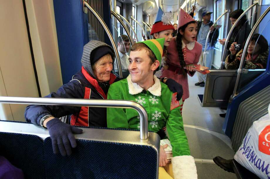 Jill Purcell smiles at Jason Broussard as 'Buddy The Elf' while riding the METRO Rail on Tuesday, Dec. 10, 2013, in Houston.  In celebration of the hit holiday show show Elf The Musical, Theatre Under The Stars and METRO have teamed up to offer a holiday treat to Houston's METRORail riders. The show runs from Dec. 6-22 at Hobby Center. Photo: Mayra Beltran, Houston Chronicle / © 2013 Houston Chronicle