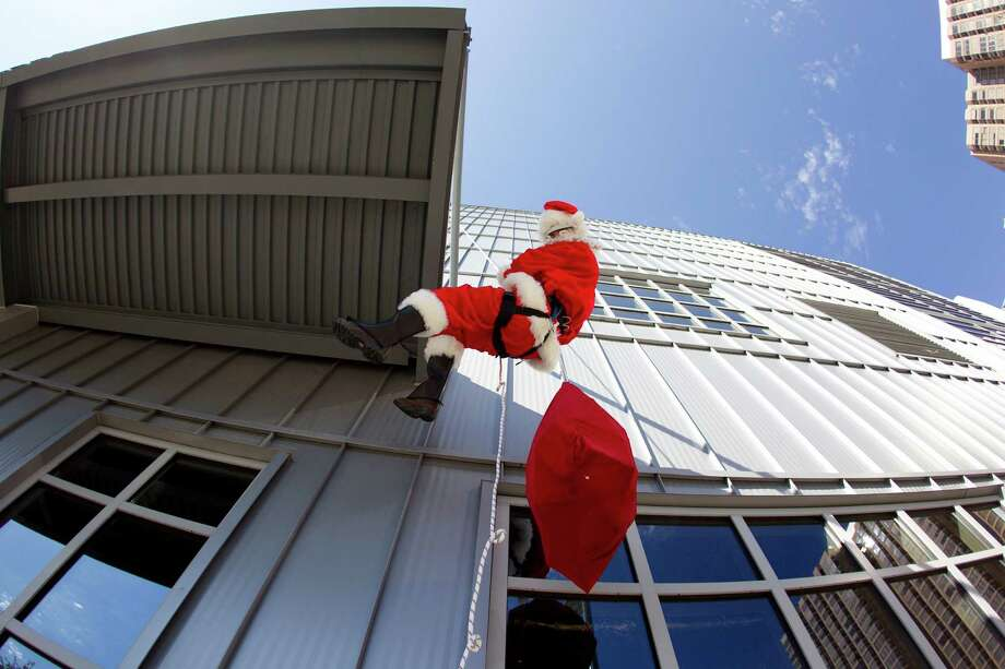 Santa Claus rappels down the three-story House of Blues building at 1204 Caroline St. to deliver holiday cheer and candy canes to a group of more than 20 third graders from Herrera Elementary School Tuesday, Dec. 10, 2013, in Houston.  The non-profit, Playworks, and GreenStreet, put on the event which included games, dancing and holiday treats. Photo: Johnny Hanson, Houston Chronicle / Houston Chronicle