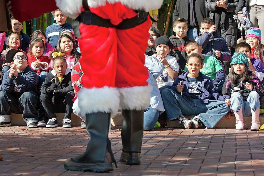 Santa Claus greets a group of more than 20 third graders from Herrera Elementary School after he rappelled down the three-story House of Blues building at 1204 Caroline St. to deliver holiday cheer and candy canes to a group of Tuesday, Dec. 10, 2013, in Houston. 