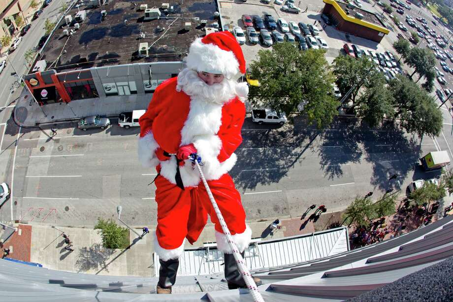 Santa Claus rappels down the three-story House of Blues building at 1204 Caroline St. to deliver holiday cheer and candy canes to a group of more than 20 third graders from Herrera Elementary School Tuesday, Dec. 10, 2013, in Houston. 