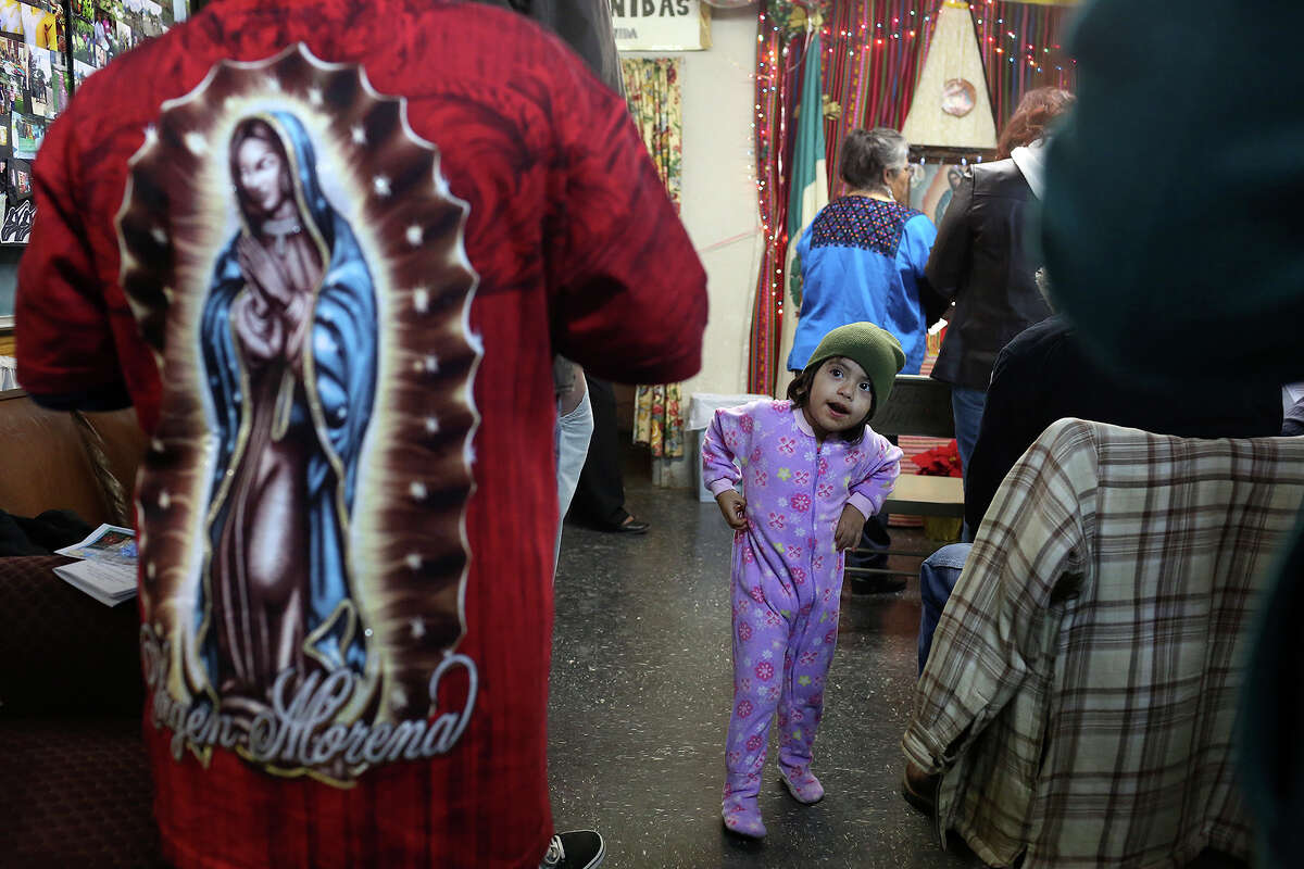 Ashley Vasquez, 3, entertains herself during Rosario a la Virgen de Guadalupe at Fuerza Unida in San Antonio on Tuesday, Dec. 10, 2013.