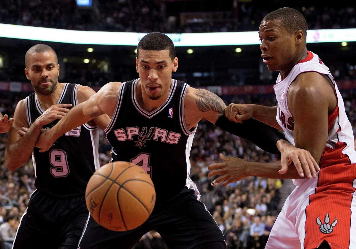 San Antonio Spurs guard Danny Green (4) battles for a rebound with teammate Tony Parker (9) and Toronto Raptors guard Kyle Lowry during the first half of an NBA basketball game in Toronto on Tuesday, Dec. 10, 2013. (AP Photo/The Canadian Press, Frank Gunn)