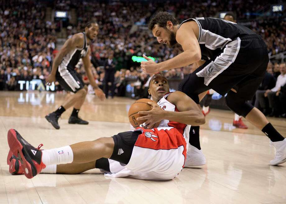 Toronto Raptors guard Kyle Lowry, bottom, battles for a loose ball with San Antonio Spurs guard Marco Melinelli during the first half of an NBA basketball game in Toronto on Tuesday, Dec. 10, 2013. (AP Photo/The Canadian Press, Frank Gunn) Photo: Frank Gunn, Associated Press / The Canadian Press