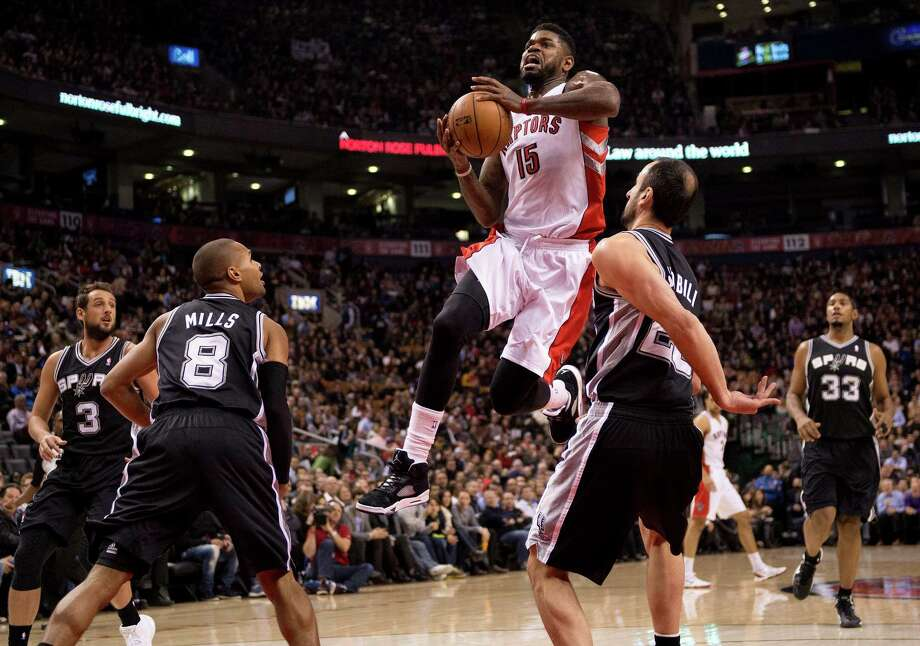 Toronto Raptors forward Amir Johnson (15) drives to the net between San Antonio Spurs guard Manu Ginobli (20) and guard Patty Mills (8) as guard Marco Belinelli (3) and forward Boris Diaw (33) stand by during the first half of an NBA basketball game in Toronto on Tuesday, Dec. 10, 2013. (AP Photo/The Canadian Press, Frank Gunn) Photo: Frank Gunn, Associated Press / The Canadian Press