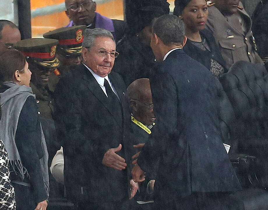 President Barack Obama and Cuban President Raul Castro prepare to exchange a handshake in South Africa. Photo: Associated Press