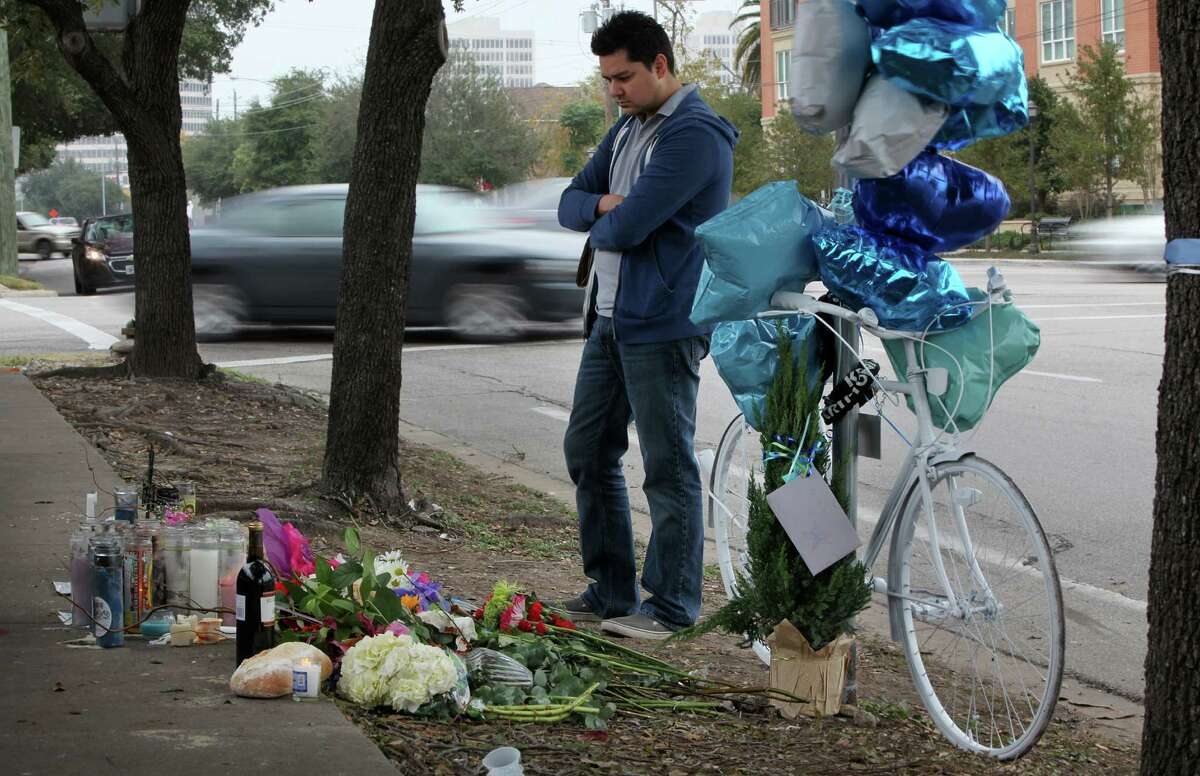 Fernando Marron leaves remembrances at the memorial for Chelsea Norman, a cyclist who was hit and killed by a motorist.