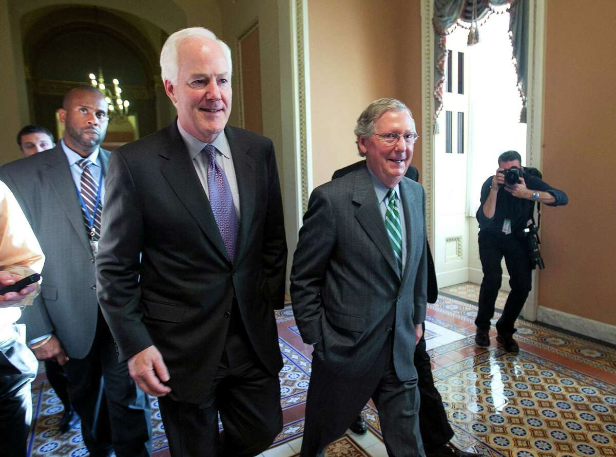 """Senate Minority Leader Mitch McConnell (R-Ky.), right, and Sen. John Cornyn (R-Texas) walk to the Senate floor for a vote in Washington, Oct. 14, 2013. Leaders in the Senate were nearing an agreement on reopening the government and raising the debt limit, as President Barack Obama warned that the country stood """"a good chance of defaulting."""" (Doug Mills/The New York Times)"""