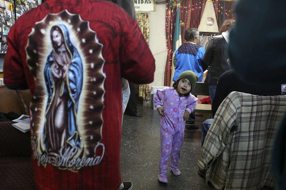 Ashley Vasquez, 3, entertains herself during the annual Rosario a la Virgen de Guadalupe at Fuerza Unida. Photo: Photos By Lisa Krantz / San Antonio Express-News