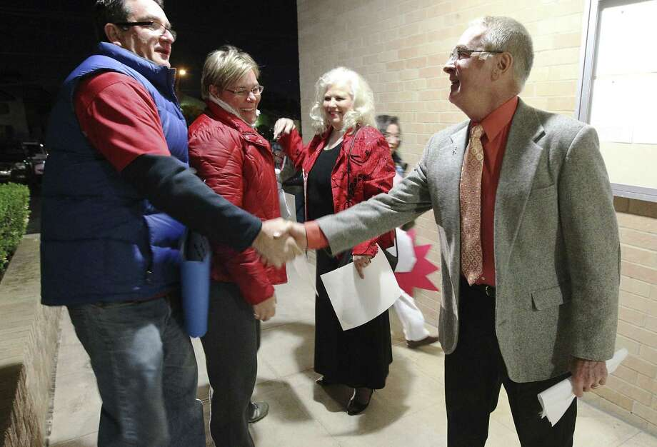 Principal Donald Powers (right) and Vice Principal Karon Wernli (second from right) are greeted by supporters before the start of the Northside ISD board meeting. Photo: Kin Man Hui / San Antonio Express-News