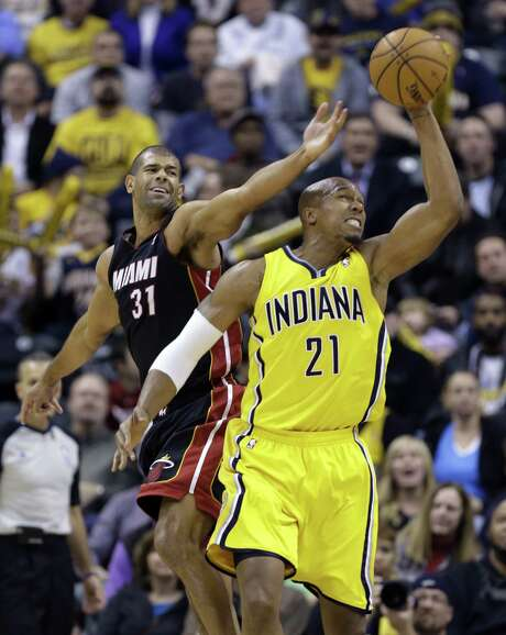 Indiana forward David West (right) grabs a long rebound in front of Miami forward Shane Battier in the second half of the Pacers' 90-84 victory. Photo: Michael Conroy / Associated Press