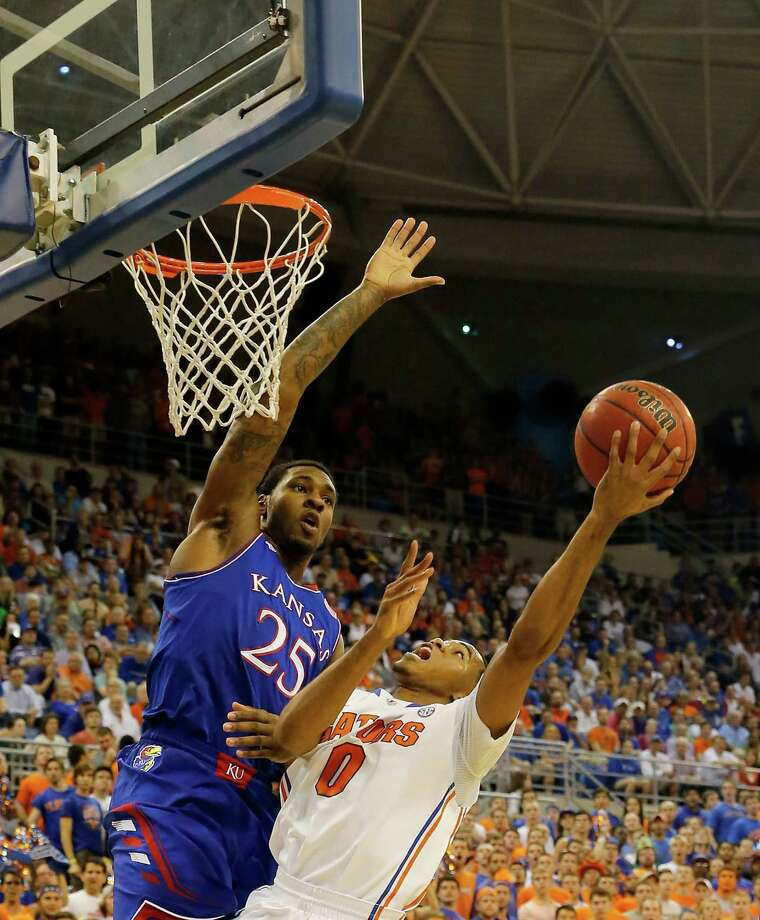GAINESVILLE, FL - DECEMBER 10:  Kasey Hill #0 of the Florida Gators drives against Tarik Black #25 of the Kansas Jayhawks during the game at Stephen C. O'Connell Center on December 10, 2013 in Gainesville, Florida.  (Photo by Sam Greenwood/Getty Images) ORG XMIT: 185396784 Photo: Sam Greenwood / 2013 Getty Images