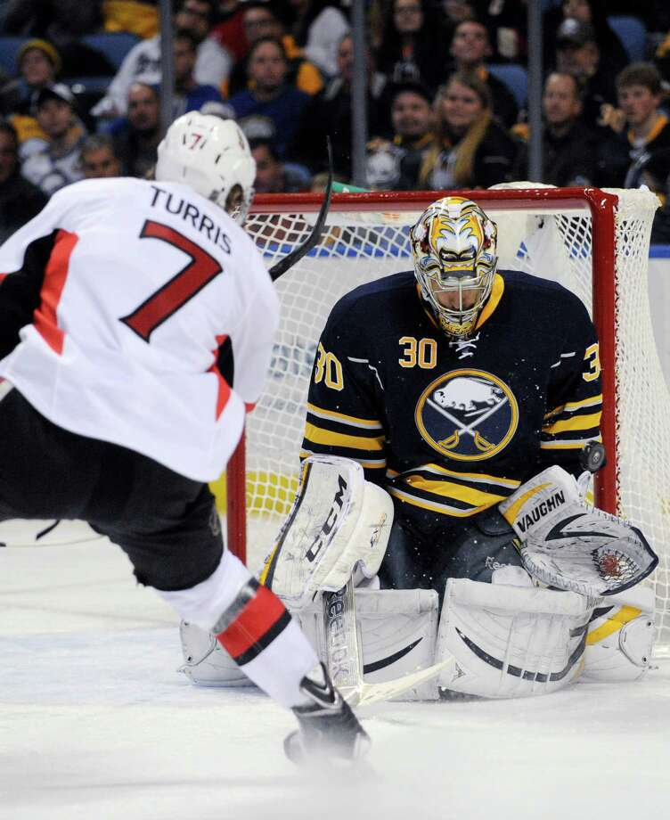 Ottawa Senators center Kyle Turris (7) hits the goal post with his shot as Buffalo Sabres goaltender Ryan Miller (30) reacts during the second period of an NHL hockey game in Buffalo, N.Y., Tuesday, Dec. 10, 2013. (AP Photo/Gary Wiepert) ORG XMIT: NYGW103 Photo: Gary Wiepert / FR170498 AP