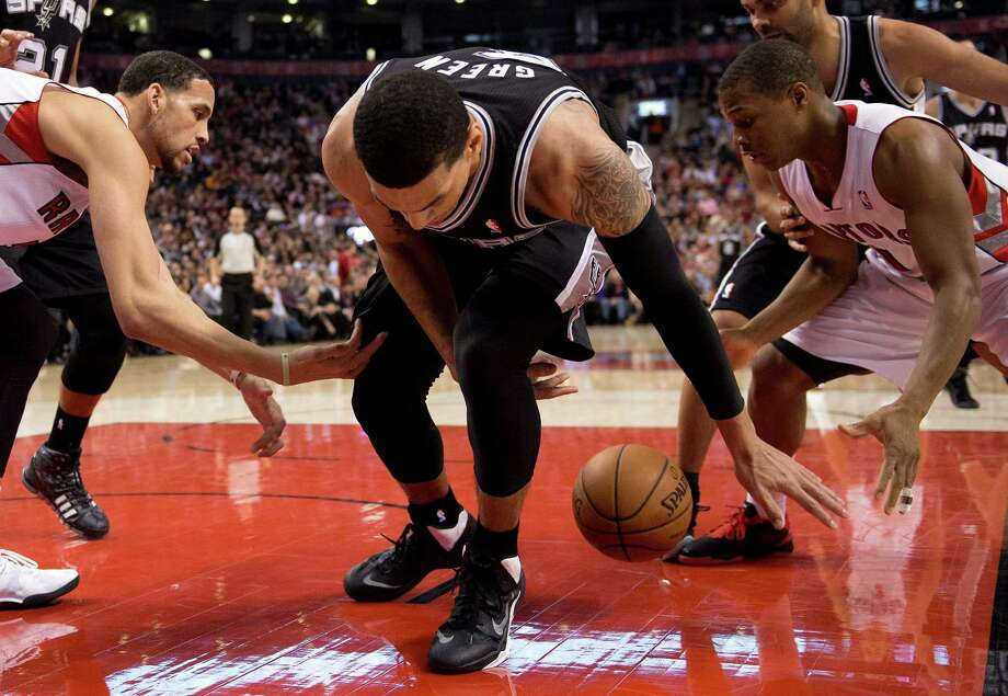 San Antonio Spurs guard Danny Green, center, loses control of the ball to Toronto Raptors guard Kyle Lowry, right, and forward Austin Daye during the first half of an NBA basketball game in Toronto on Tuesday, Dec. 10, 2013. (AP Photo/The Canadian Press, Frank Gunn) Photo: Frank Gunn, Associated Press / The Canadian Press