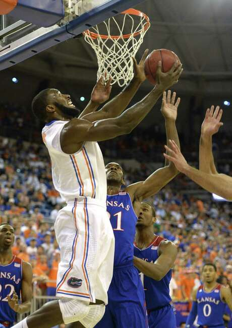 Florida's Patric Young goes up to score from under the basket as Kansas center Joel Embiid arrives too late. Photo: Phil Sandlin / Associated Press