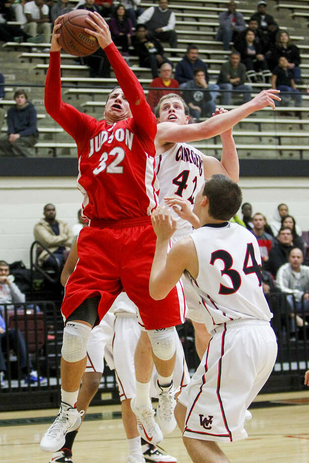 Judson's Tanner Leissner (left) pulls down a rebound over Churchill's Brian Herring (middle) as Jeff Fesperman looks on. Photo: Marvin Pfeiffer / San Antonio Express-News