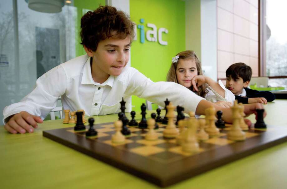 Frederico Gazal, 11, plays chess as his sister, Gigi, 9, and brother, Leo, 6, look on during a grand opening ceremony for Zaniac, a kid's learning center, in Greenwich, Conn., on Tuesday, December 10, 2013. Photo: Lindsay Perry / Stamford Advocate