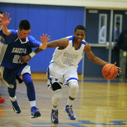 Shaker's Will Francis brings the ball up the court during their high school boy's basketball game ag