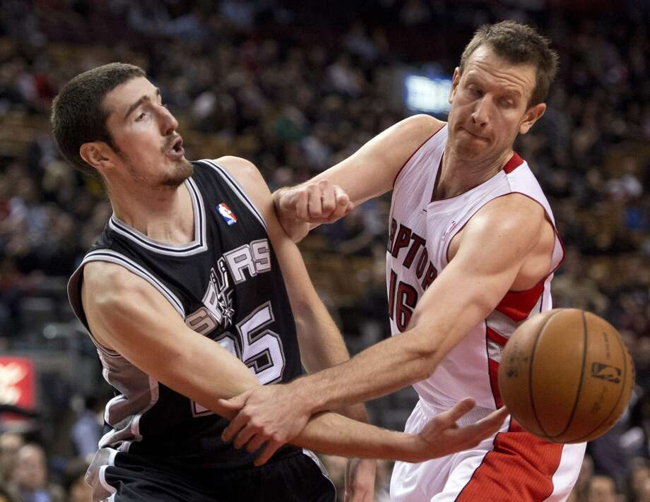 San Antonio Spurs guard Nando De Colo, left, passes the ball past Toronto Raptors forward Steve Novak (16) during the second half of an NBA basketball game in Toronto on Tuesday, Dec. 10, 2013. (AP Photo/The Canadian Press, Frank Gunn) Photo: Associated Press