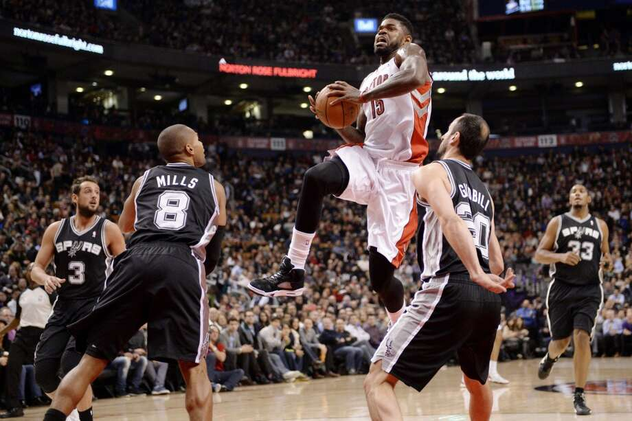 Toronto Raptors forward Amir Johnson (15) drives to the net between San Antonio Spurs guard Manu Ginobli (20) and guard Patty Mills (8) as guard Marco Belinelli (3) and forward Boris Diaw (33) stand by during the first half of an NBA basketball game in Toronto on Tuesday, Dec. 10, 2013. (AP Photo/The Canadian Press, Frank Gunn) Photo: Associated Press