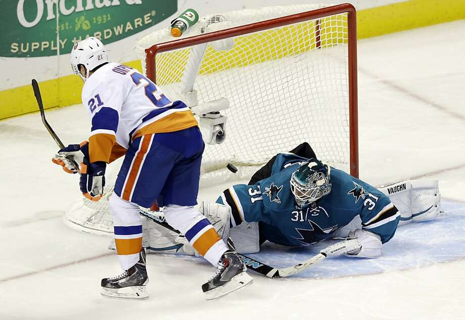Kyle Okposo (21) scores past Sharks goalie Antti Niemi to lift the Islanders in the fourth round of the shootout and snap a 10-game winless streak. Photo: Marcio Jose Sanchez, Associated Press