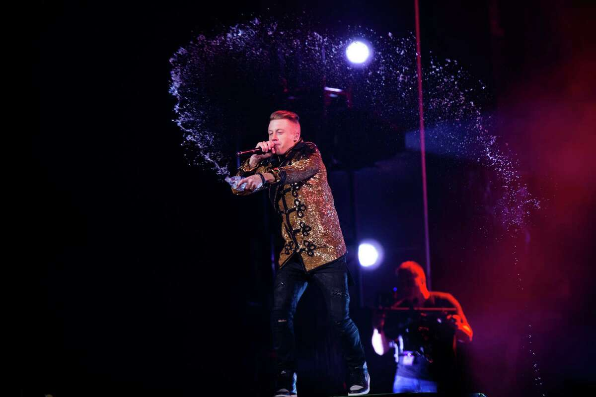 Seattle musicians Macklemore throws water as he performs with Ryan Lewis and their posse at KeyArena for a hometown crowd during the last stop of their fall