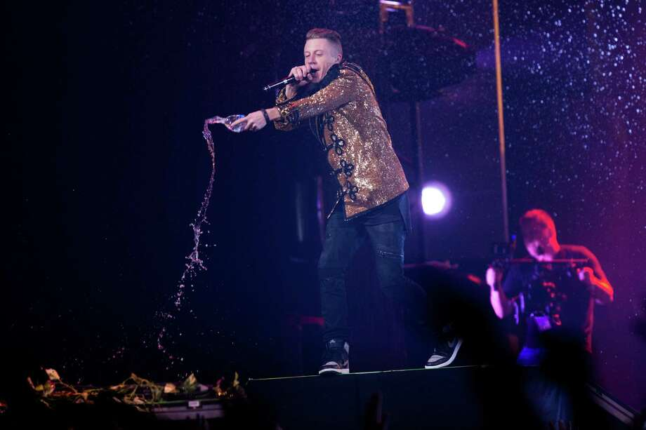 Seattle musicians Macklemore throws water as he performs with Ryan Lewis