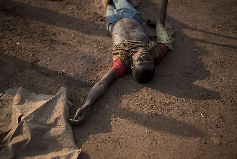 The body of a victim lies on a street in Combattant neighbourhood near the airport in Bangui on December 10, 2013. French President Francois Hollande arrived in the Central African Republic on a mission to shore up the morale of a French intervention force after the death of two of the country's elite soldiers. The first losses of the French campaign to pacify its former colony underlined the risks involved in a complex mission to disarm rogue rebels who have plunged the impoverished country into chaos. TOPSHOTS/AFP PHOTO / FRED DUFOUR