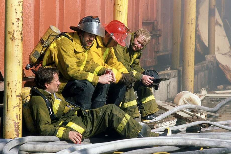 Firefighters take a breather following an explosion at the Borden's Ice Cream plant. Photo: John Everett, Houston Chronicle