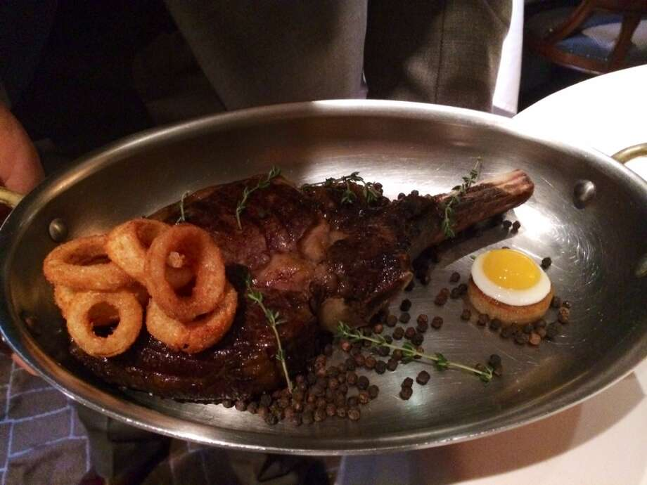 Steak and eggs presented tableside: a 100-day dry-aged chunk of meat with onion rings and quail eggs