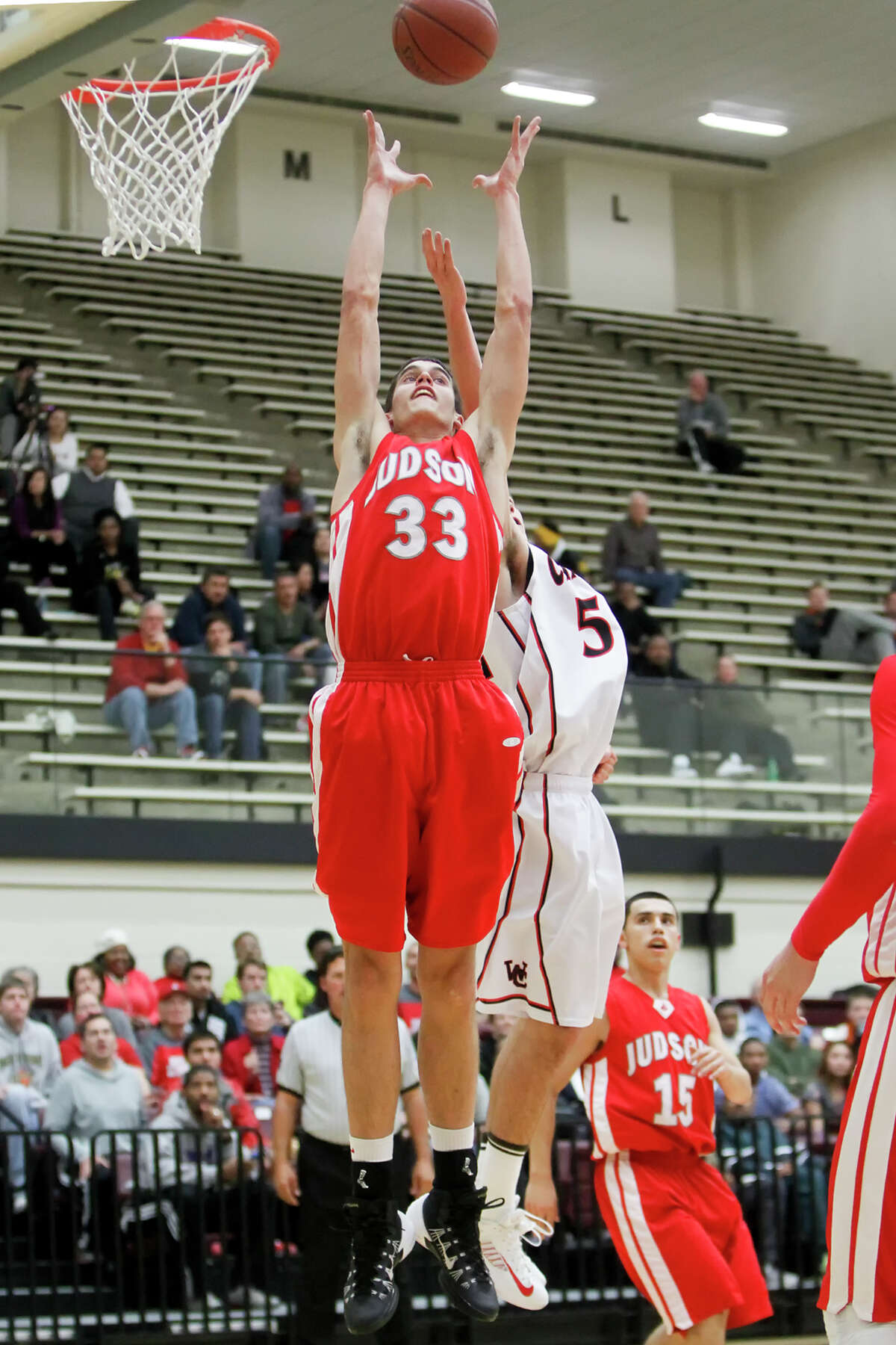 Judson's David Wacker (left) stretches for a rebound over Churchill's Braeden Bernstein during the first half of their game at Littleton Gym on Tuesday, Dec. 10, 2013. Judson beat the Chargers 58-55. MARVIN PFEIFFER/ mpfeiffer@express-news.net